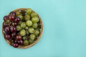 vista de cima de uvas em uma cesta em fundo azul com espaço de cópia