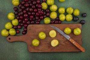 vista superior de ameixas de cereja verdes em uma placa de cozinha de madeira