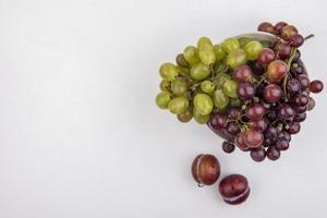 vista superior das uvas em uma tigela sobre fundo branco com espaço de cópia foto