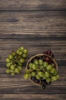 vista superior das uvas na cesta e no fundo de madeira com espaço de cópia foto