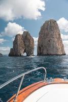 barco branco e marrom em direção à formação rochosa