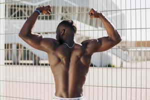 negro apto mostrando os músculos das costas