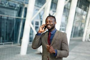 Elegante empresário negro afro-americano falando em seu smartphone