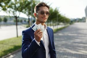 homem segurando muito dinheiro