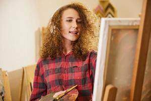 linda garota ouve música com fones de ouvido e canta enquanto pinta