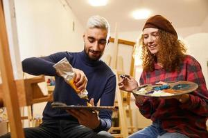 garota encaracolada e homem loiro pintando e sorrindo