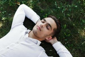 jovem bonito em uma camisa branca deitado no chão