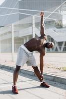 bonito homem afro-americano fazendo alongamento antes de um treino ao ar livre