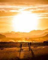 três homens nas dunas de areia durante a hora dourada
