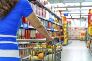 senhora empurrando um carrinho de compras no supermercado. foto