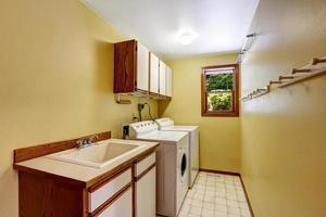 lavanderia amarela brilhante com armários e pia
