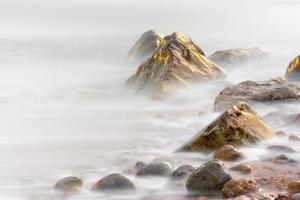 rochas em Osmington refletindo as cores do pôr do sol foto