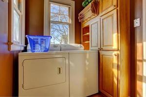 pequena lavanderia com lavadora e secadora