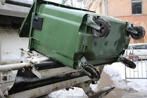 a lata de lixo e veículo de coleta de lixo foto