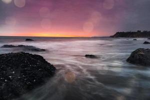 ondas quebrando sobre rochas cobertas musculosas foto
