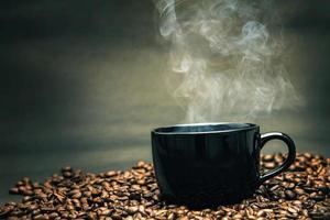 xícara de café preto quente em grãos torrados