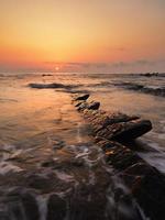 rock na praia de Barrika ao pôr do sol foto