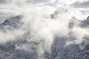 nuvens pairam sobre os picos das montanhas foto