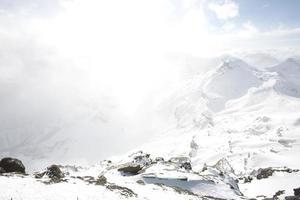 poeira de neve se acumula sobre o pico da montanha foto