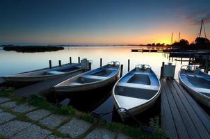 nascer do sol no porto do lago com barcos foto