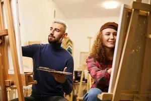 homem e mulher desenham pinturas em cavaletes