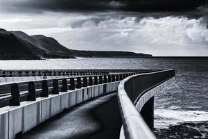 foto em tons de cinza de uma ponte sobre o oceano