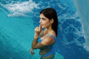 menina em pé na piscina foto