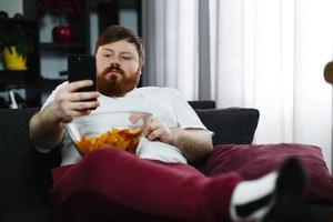 homem comendo batatinhas enquanto verifica o telefone