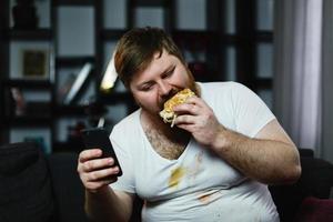 homem verifica algo em seu smartphone enquanto come um hambúrguer