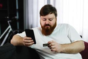 homem gordo digita o número de um cartão de crédito em seu telefone