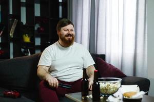 homem sorri enquanto está sentado no sofá com petiscos