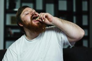 close-up de um homem gordo enquanto ele come pipoca
