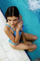 menina sentada na beira da piscina