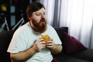 homem gordo sorridente comendo hambúrguer sentado em frente a um aparelho de TV