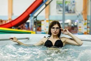linda garota relaxando em um parque aquático foto