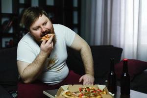 homem gordo feio comendo pizza sentado no sofá