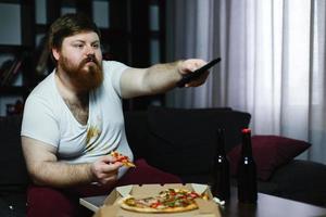 homem gordo come pizza sentado no sofá