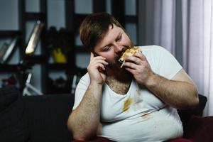 homem comendo um hambúrguer enquanto fala ao telefone