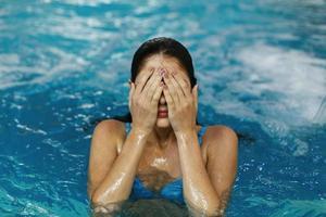garota cobrindo os olhos na piscina foto