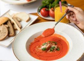 mulher comendo sopa de tomate