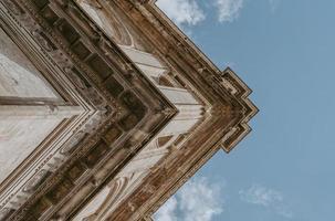fotografia de baixo ângulo de um edifício bege sob o céu azul