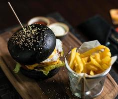 hambúrguer de pão preto com batata frita foto