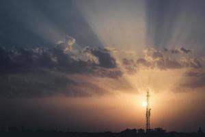 pôr do sol colorido com a silhueta de uma torre