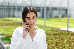 pesquisador fala ao telefone andando em volta de uma estufa
