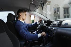 empresário sorridente sentado dentro do carro