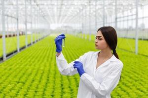 pesquisadora segurando um tubo de vidro