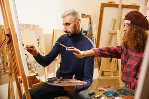 garota de cabelo encaracolado e homem pintando