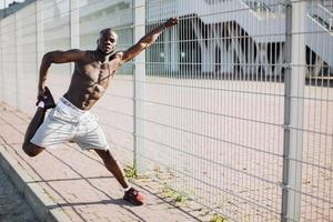 homem negro se espreguiçando em uma cerca