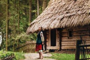 garota em um vestido bordado está parada no quintal olhando para o céu