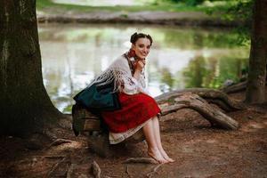 jovem com um vestido bordado étnico sentada em um banco perto do lago